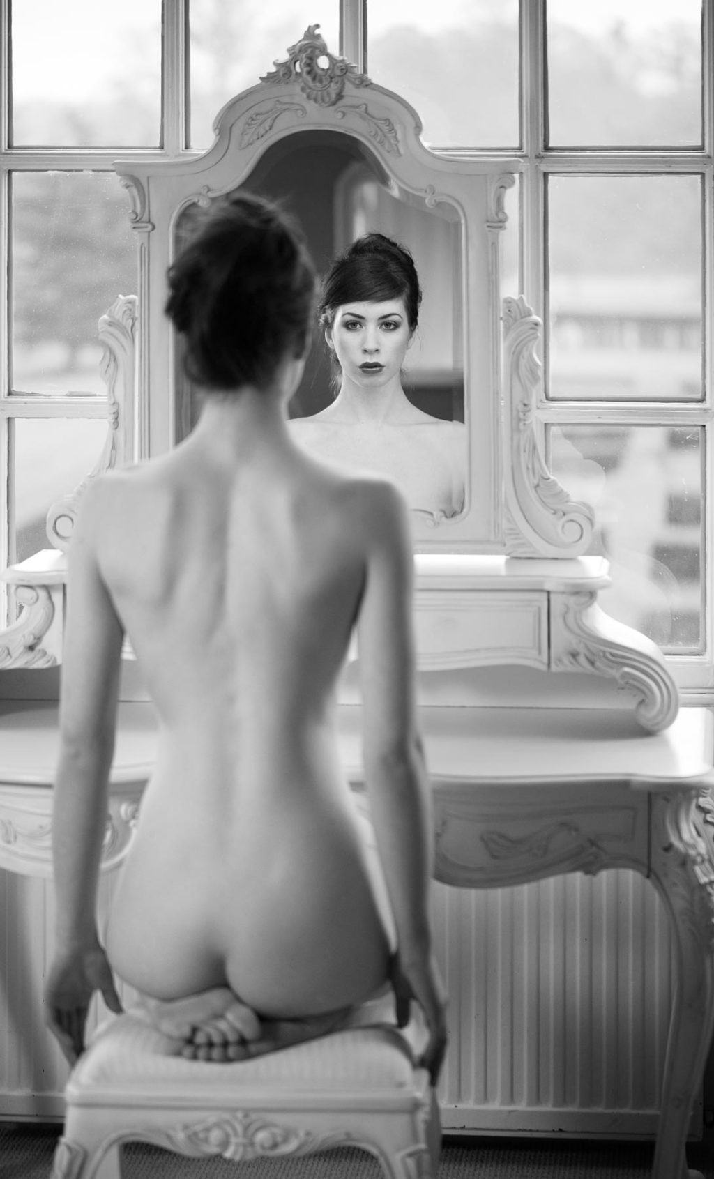 Elle Beth sitting naked in front of a mirror
