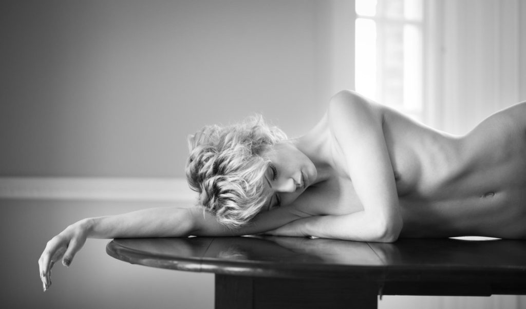 Katy lies on a polished dining table
