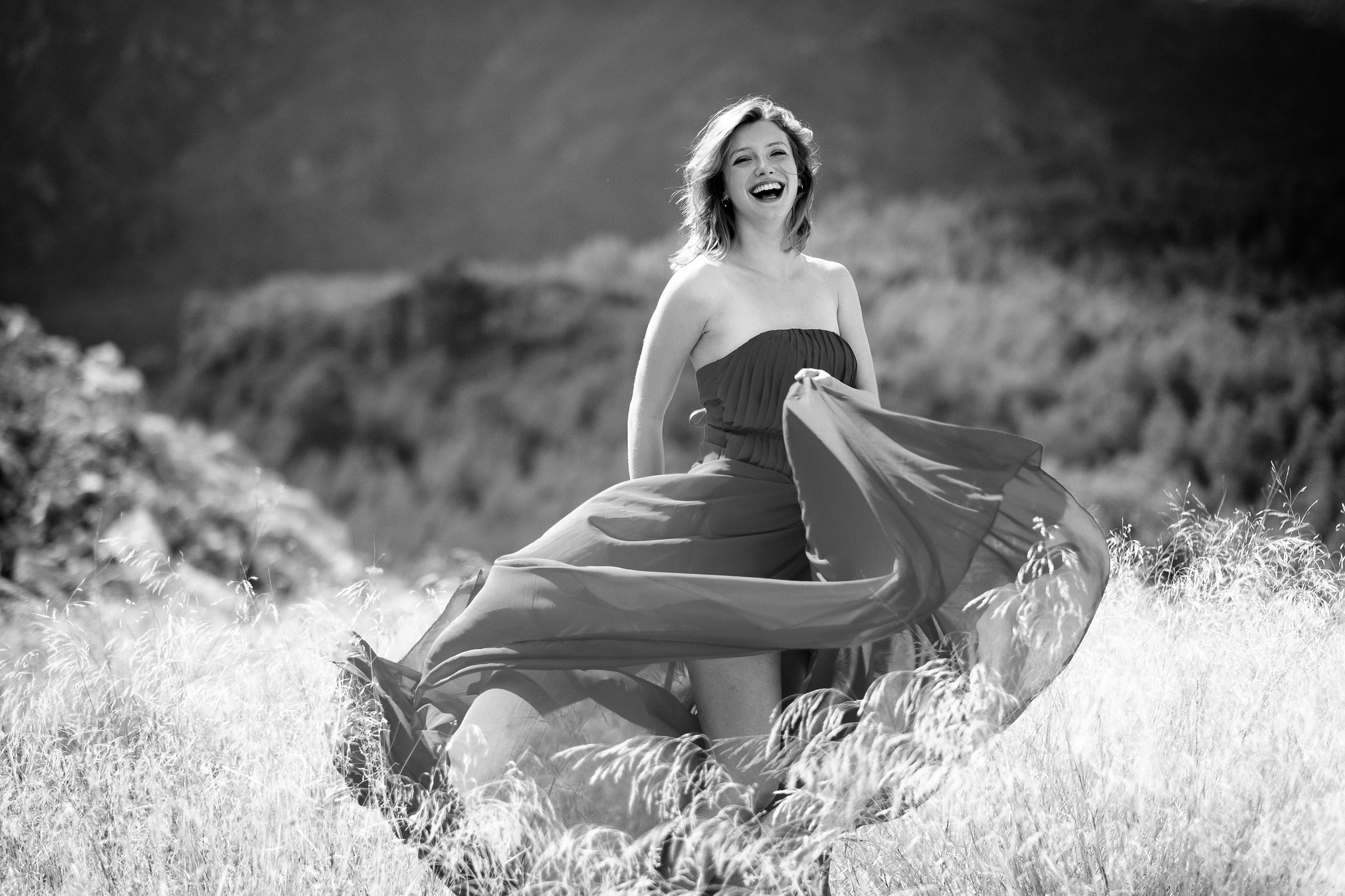 Claire Rammelkamp wafting a dress in long grass in Spain.