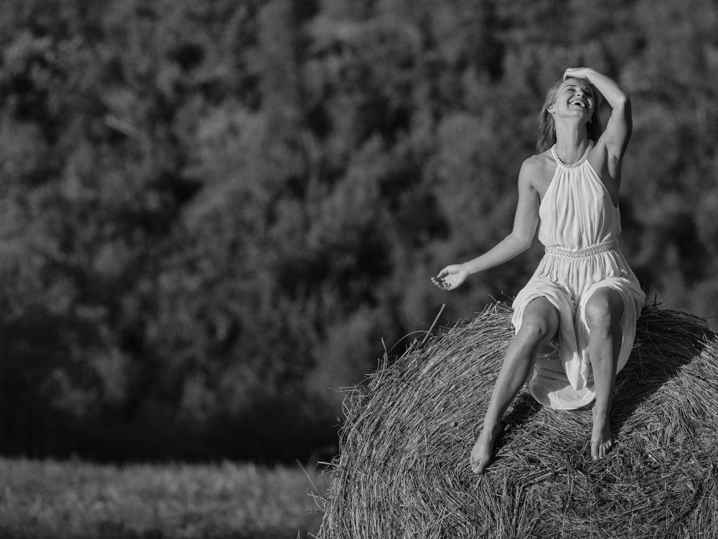 Terez in hysterics on a bale of hay in Tuscany