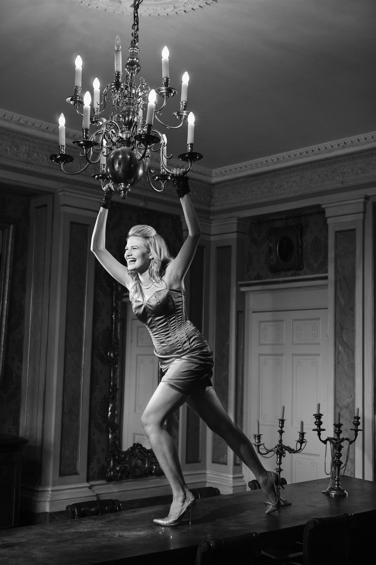 Chloe-Jasmine Whichello swinging from a chandelier in Maunsel House Somerset.