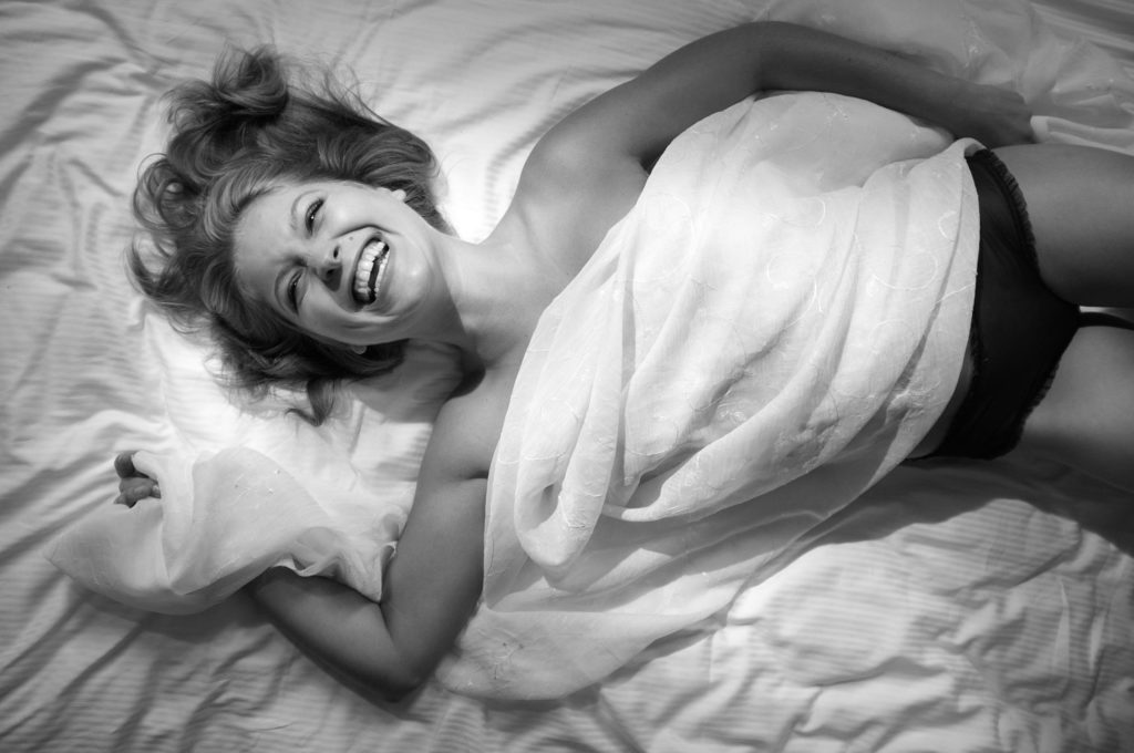Wlada laid out on the bed with a piece of sheer fabric covering her