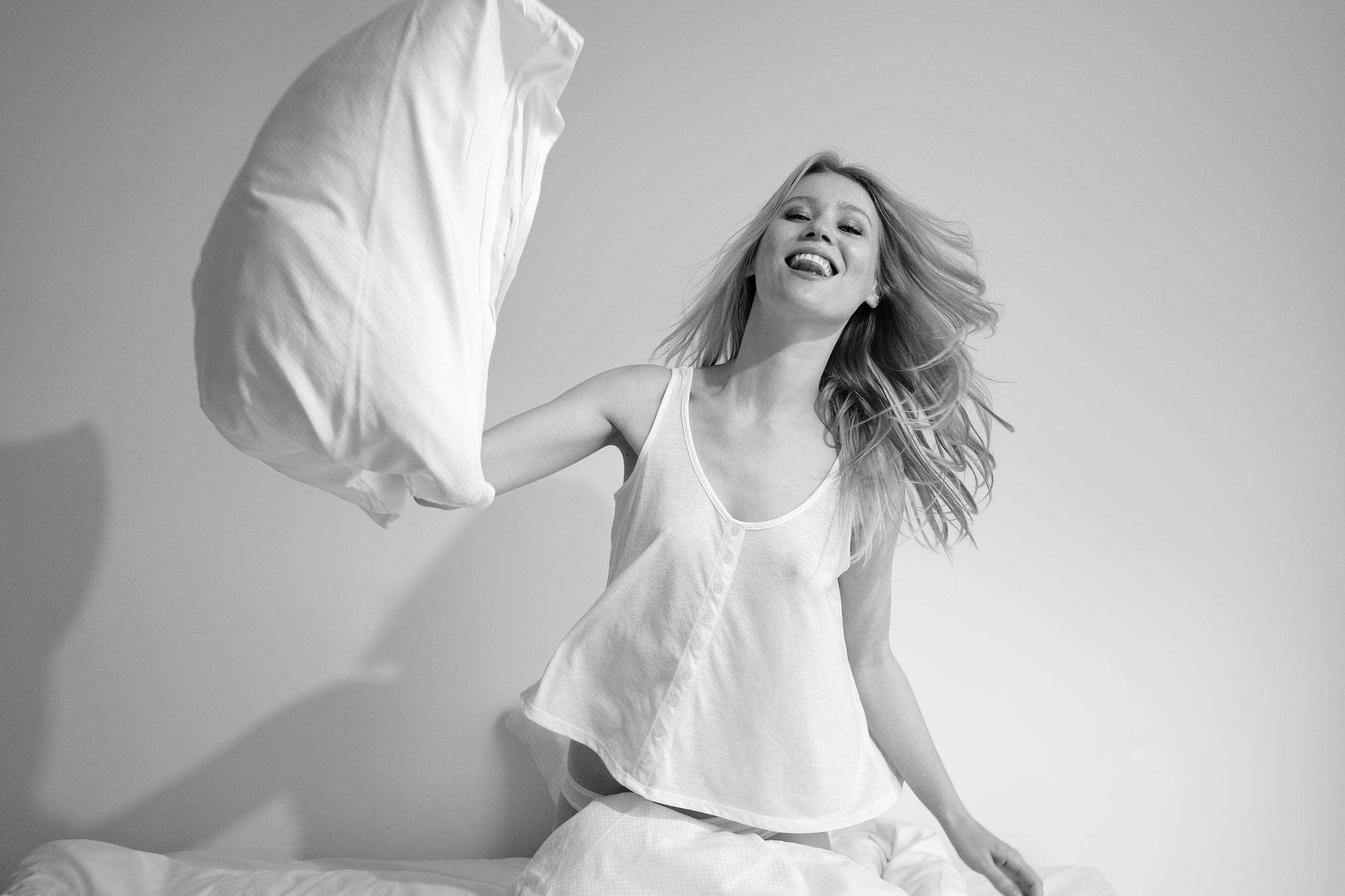 Melanie Beckendorff-Leavens having a pillow fight in an apartment in Copenhagen. Monochrome print by Damien Lovegrove