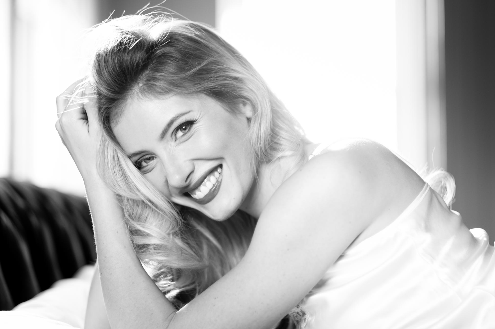 Victoria from Taunton, Somerset lying on a bed laughing. A photograph by Damien Lovegrove.