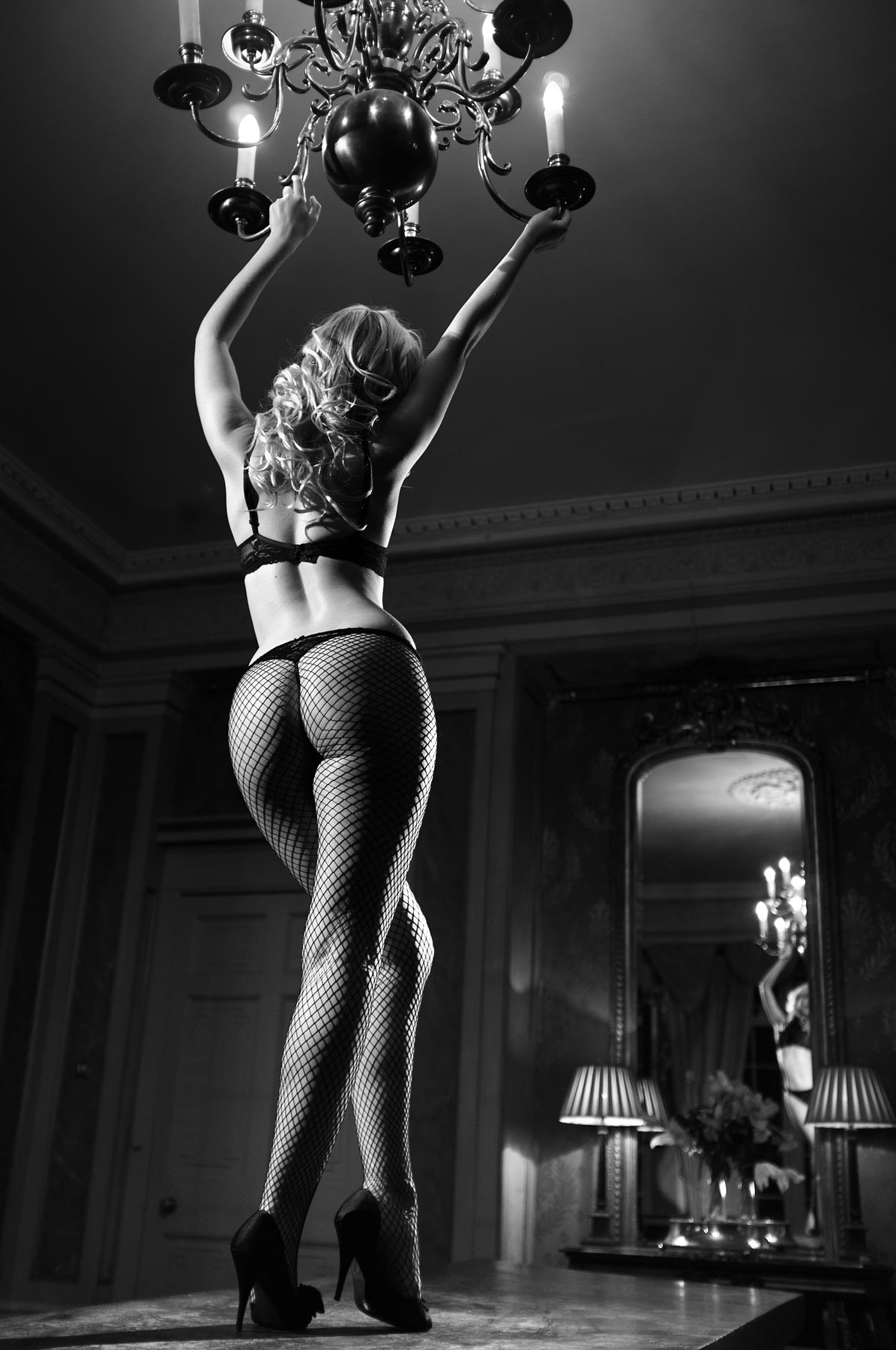 Raphaella McNamara on a table in fishnet tights swinging from a chandelier - Monochrome