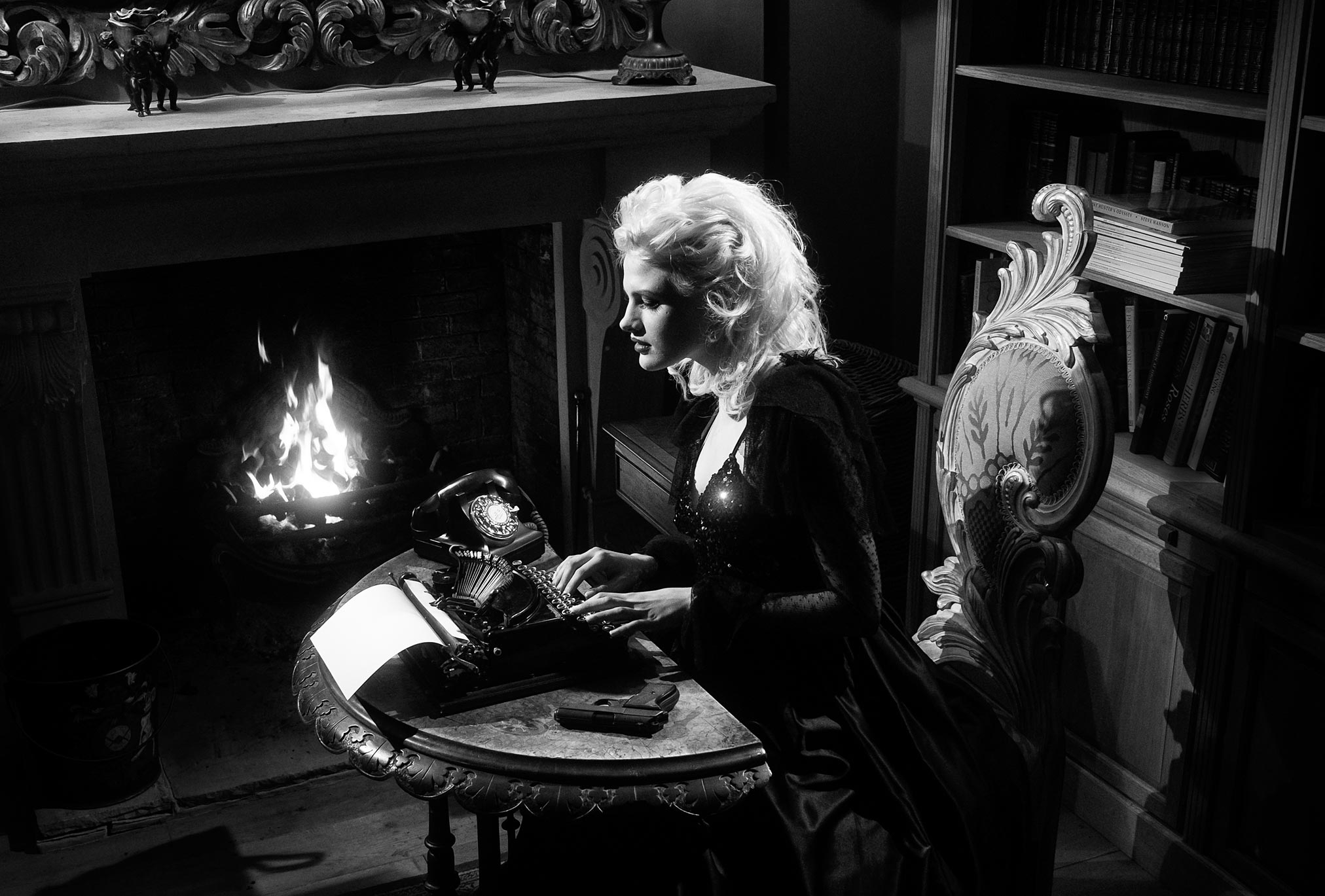 Chloe-Jasmine Whichello by a fireside with a gun