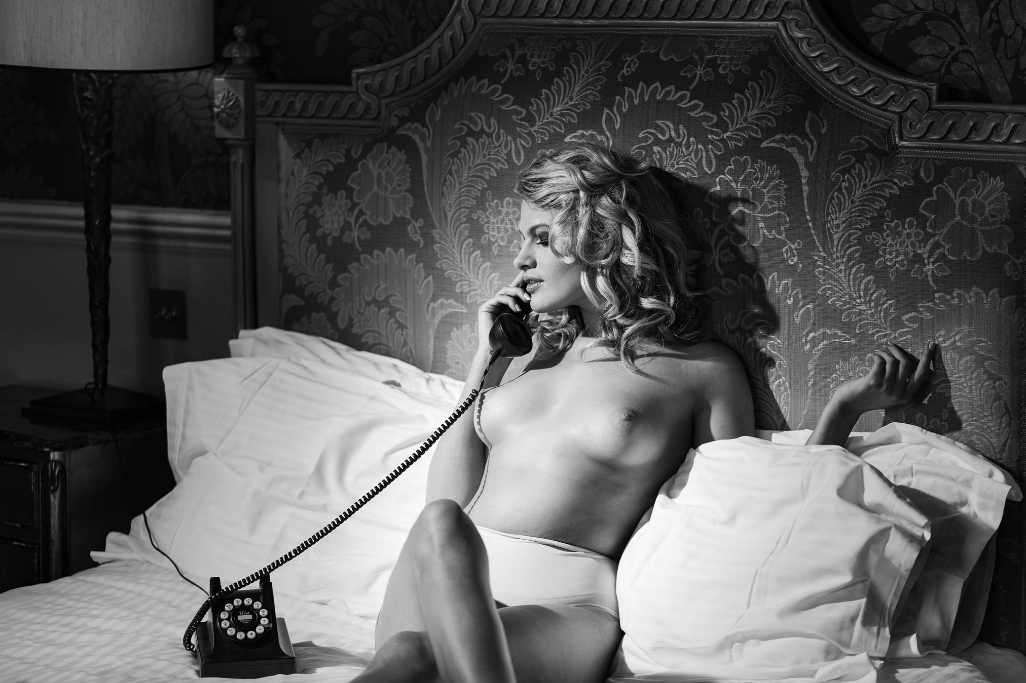 Chloe Jasmine naked on the bed making a phone call. Monochrome