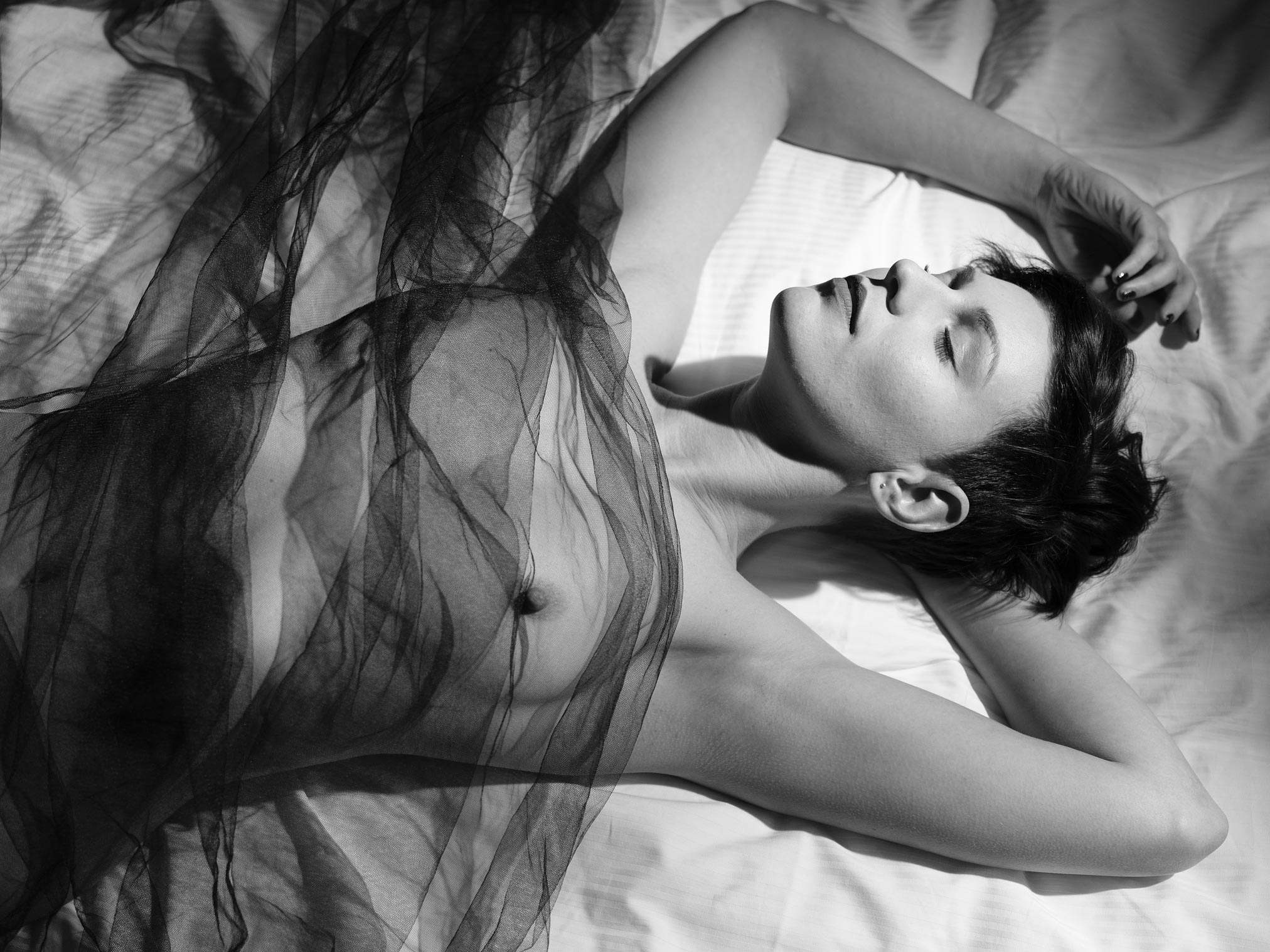 This picture of a Misha lying on a bed with a sheer cloth covering her like a veil.