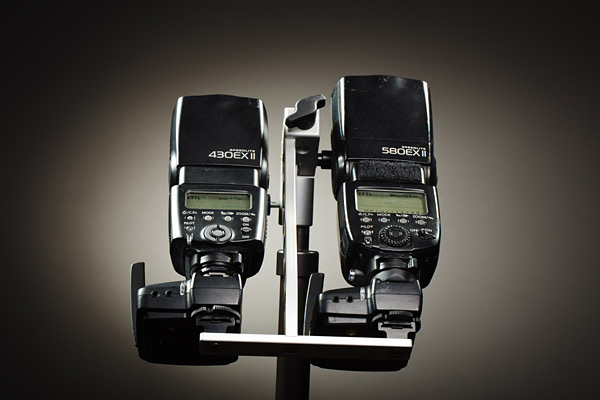 The asymetric foot plate allows a perfect clearance for the Pocket Wizard Flex units and keeps the Speedlight heads close and parallel to the umbrella shaft.