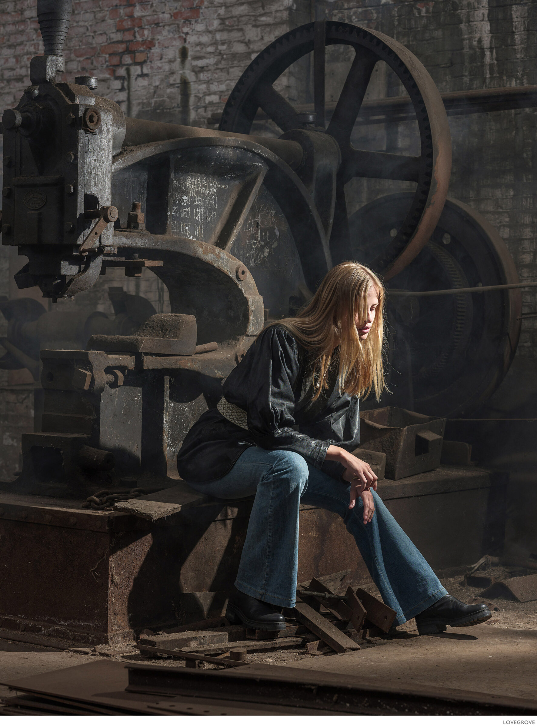 Jolien sits on a machine in this industrial age workshop